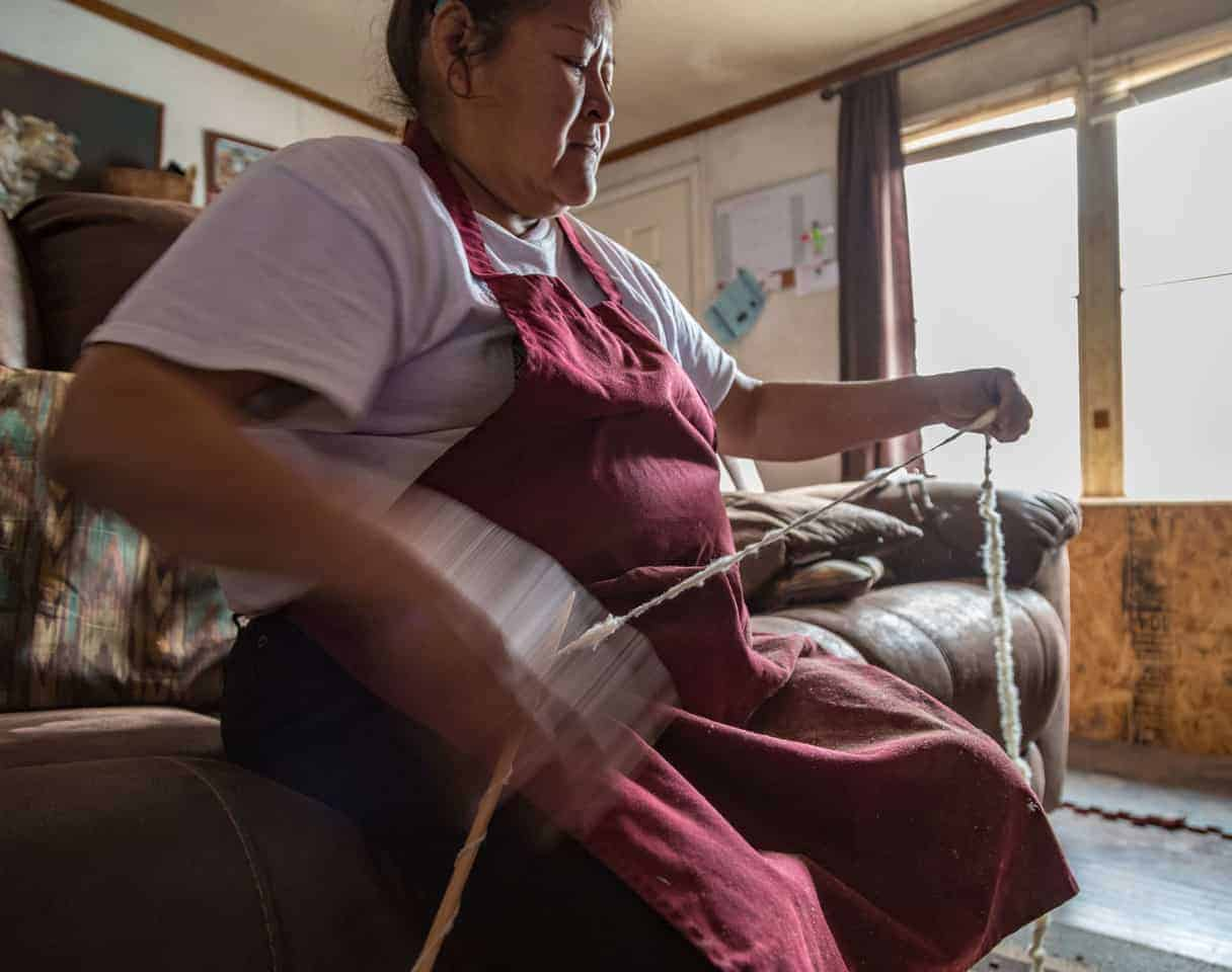 A Native American woman spinning cream-colored yarn.