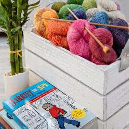 A box of brightly colored yarn next to a book.