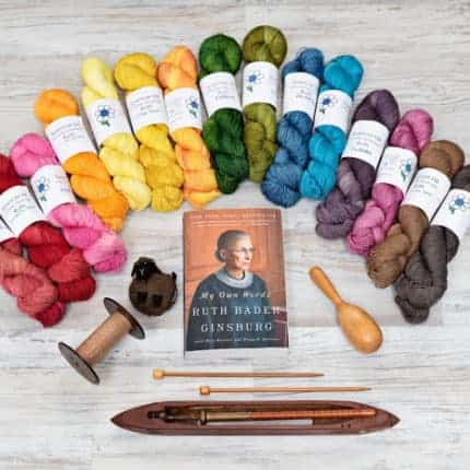 A rainbow of yarn above a book featuring Ruth Bader Ginsburg.
