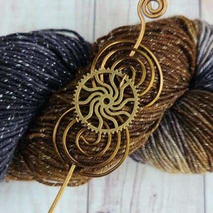 A bronze shawl pin on sparkly blue and brown yarn.