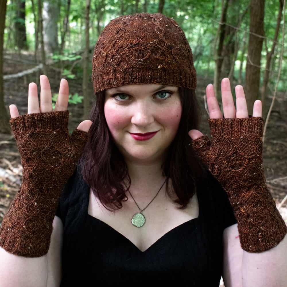A woman models a brown cabled hat and mitts.