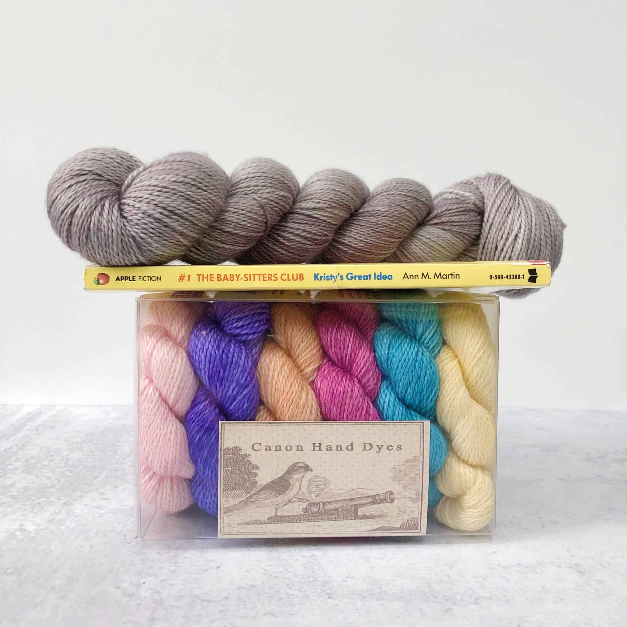 Gray yarn atop a book and a box of colorful mini skeins.