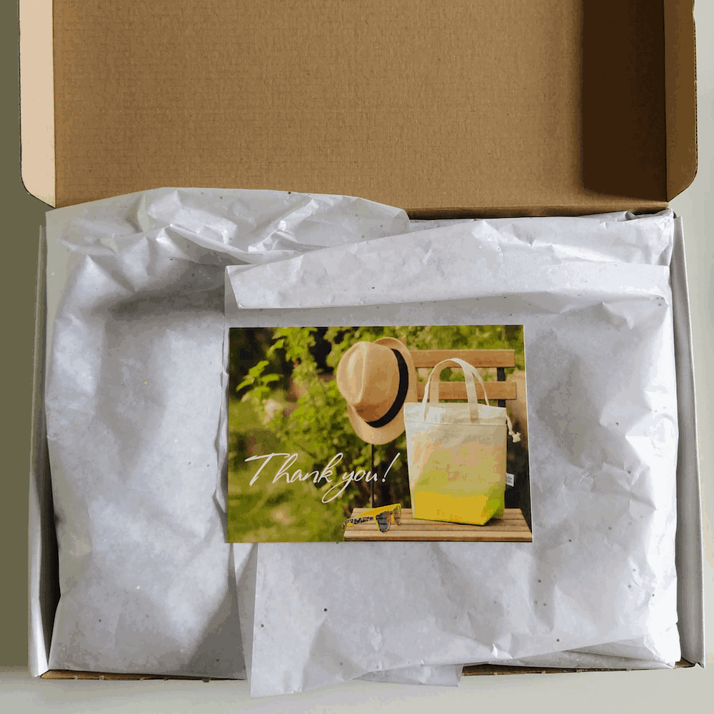 A box with a photo of a yellow tote and straw hat.