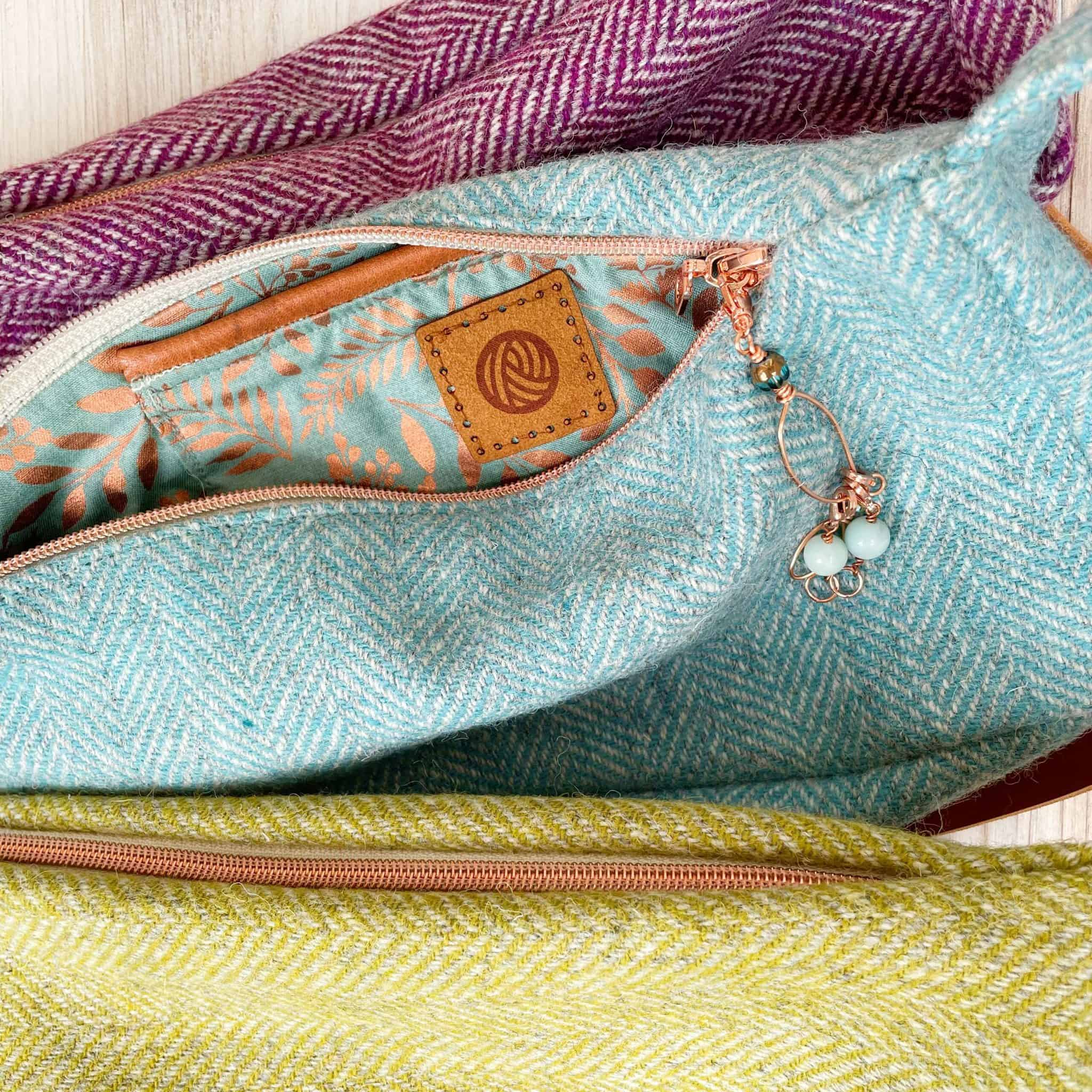 Purple, teal and green tweed bags with rose gold zippers.