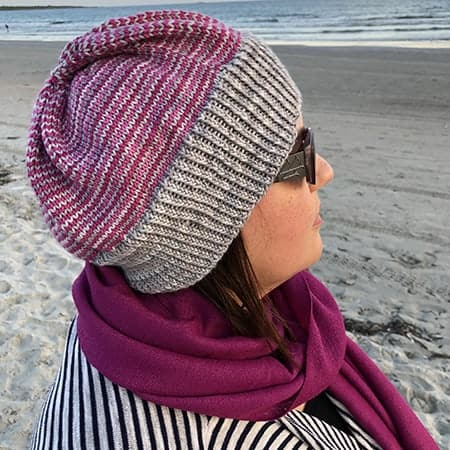 A woman models a purple and gray hat on a beach.