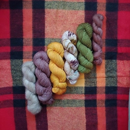 Yarn on a plaid blanket.