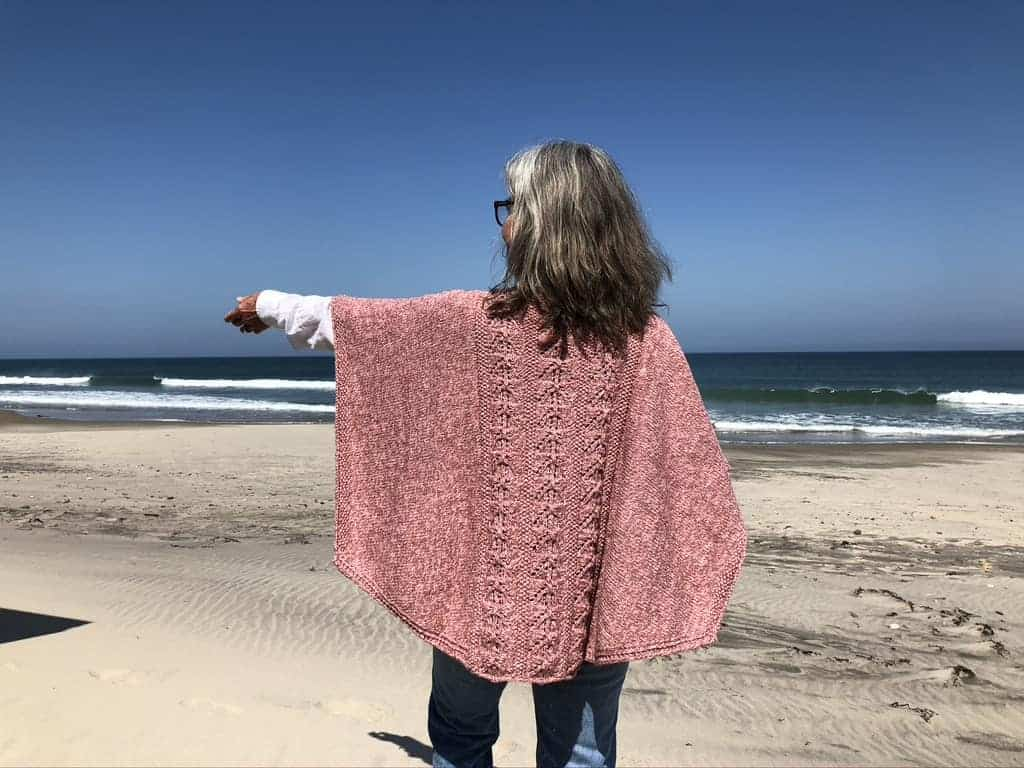 A pink cabled poncho modeled on a beach.