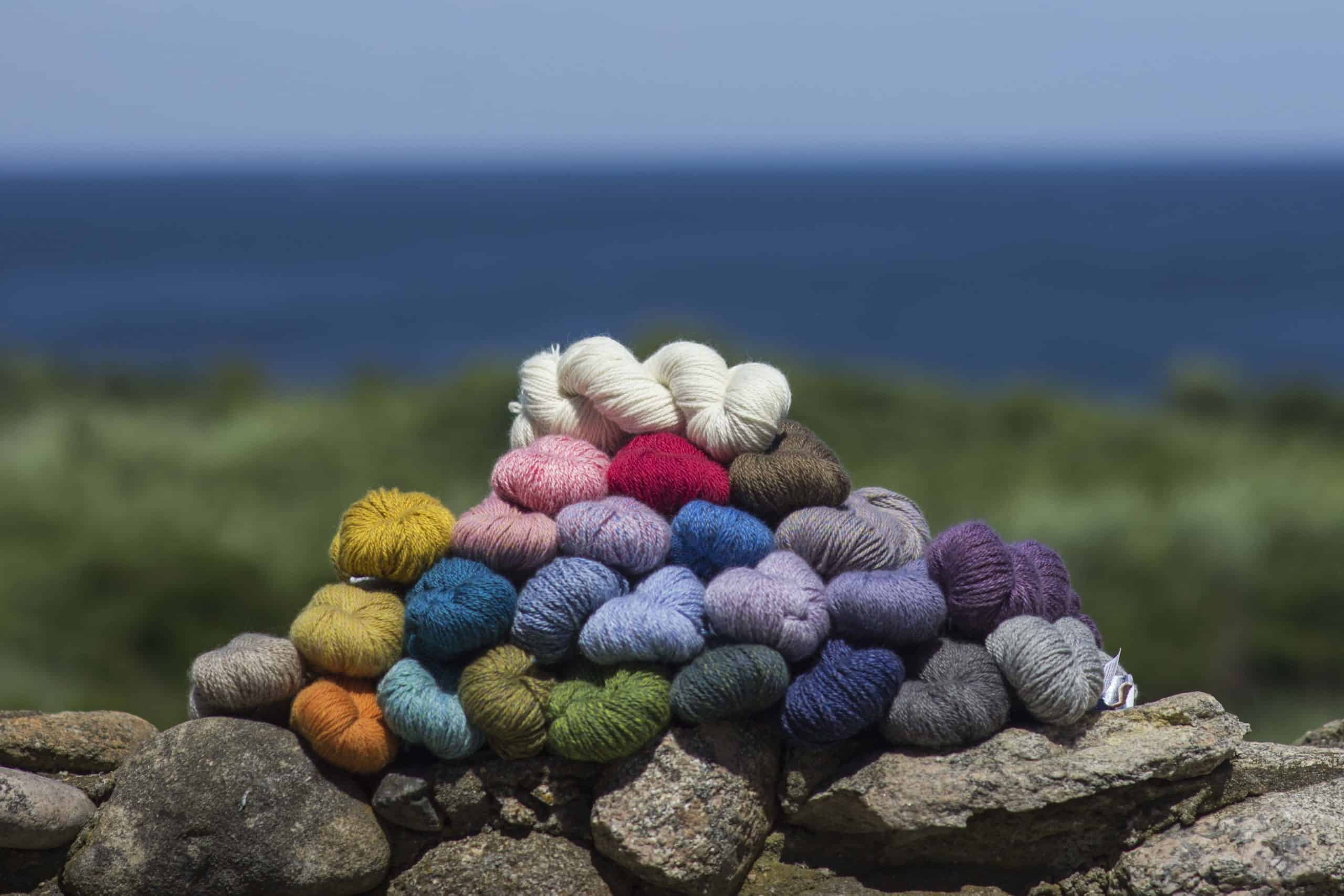A pile of colorful yarn sitting on a rock.