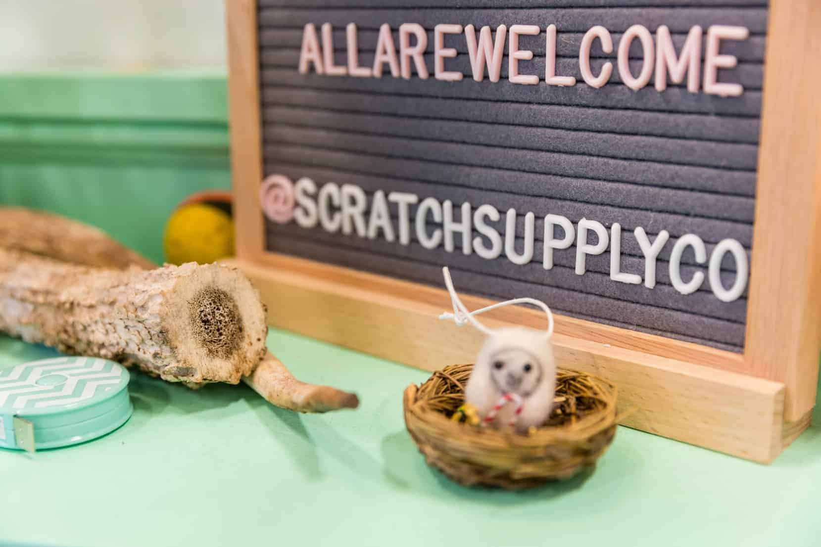 A letter sign that reads ALLAREWELCOME and @SCRATCHSUPPLYCO in pink and white.