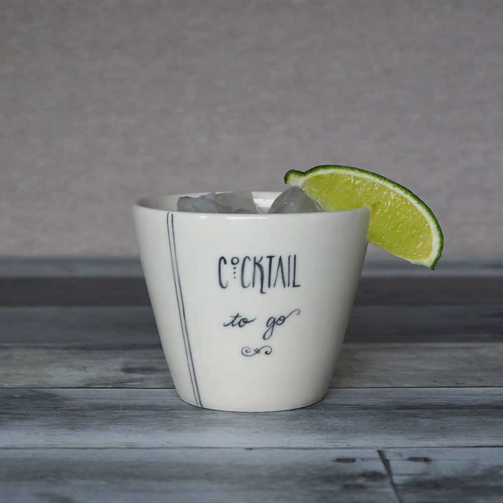 A white porcelain cup with a lime wedge and the words Cocktail To Go.