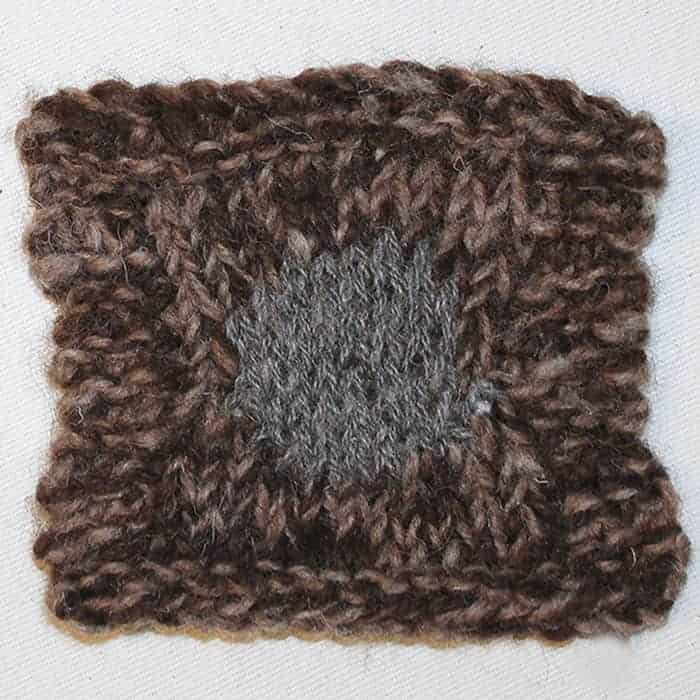 A brown knitted square with a circle of gray.