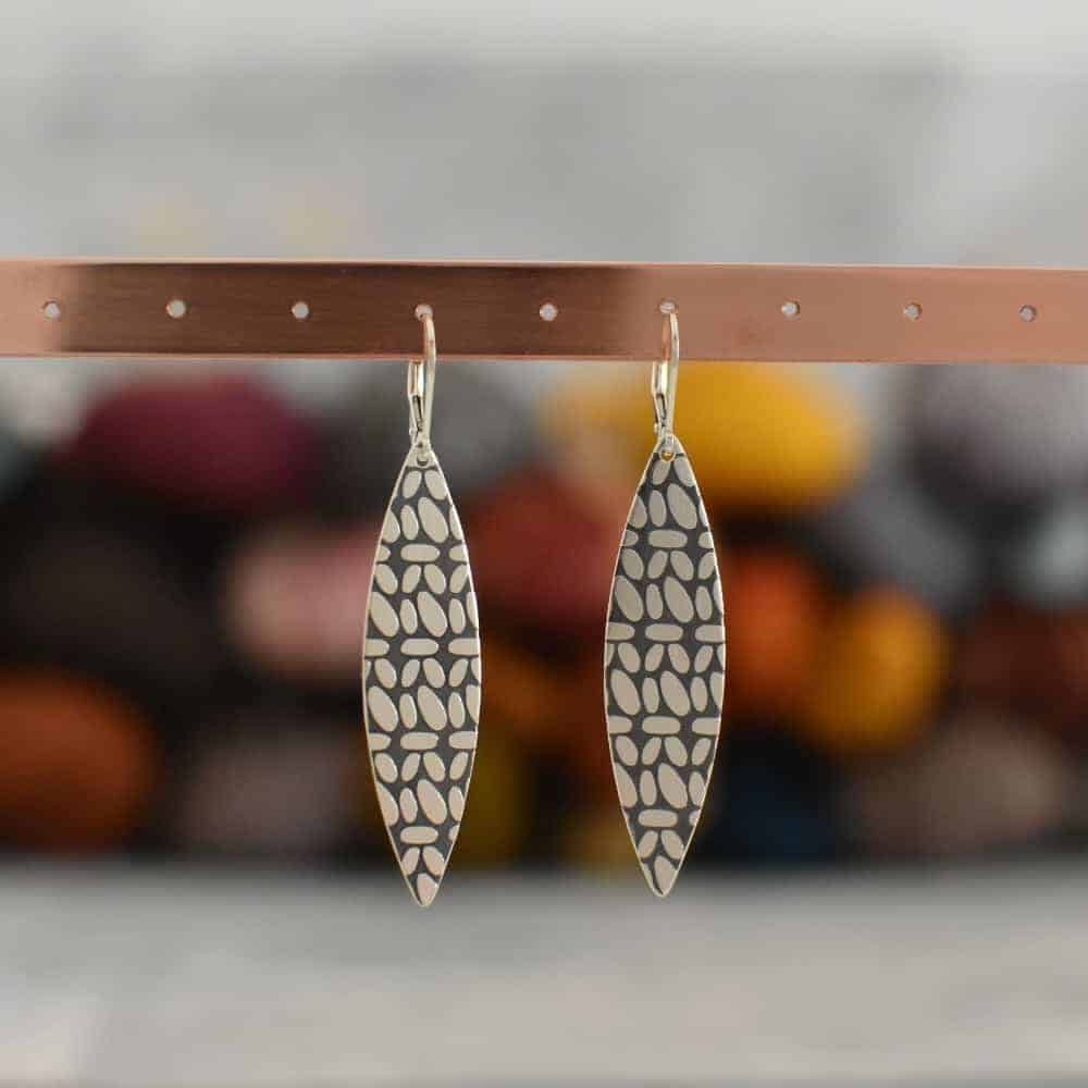 Leaf shaped earrings with etched knitting stitches.