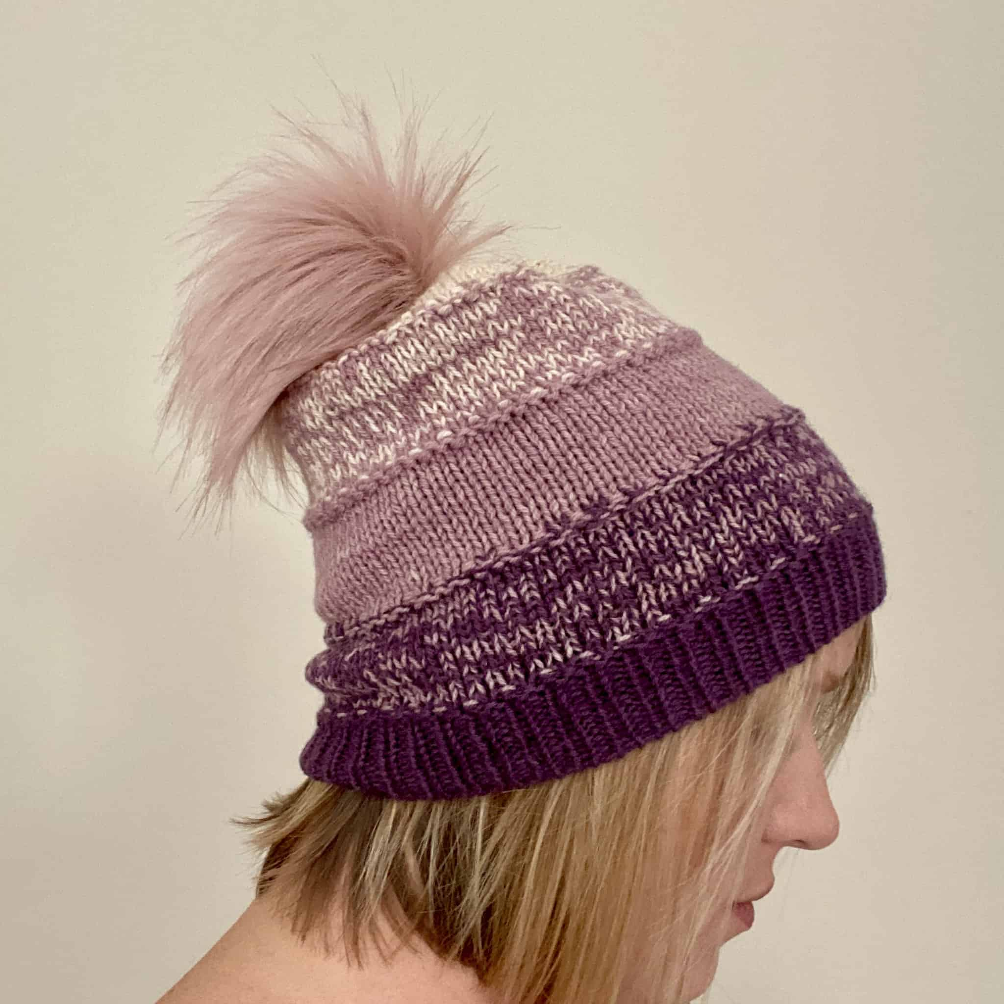 A plum and pink hat with a pink pom pom.