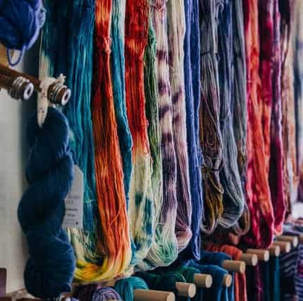 Colorful hanks of yarn hanging untwisted.
