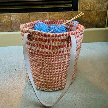 A pink basket with a strap.