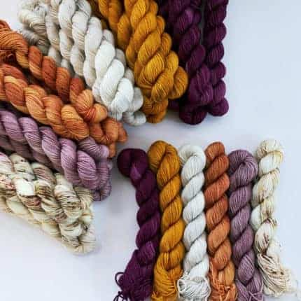 Skeins of orange, purple and white yarn.