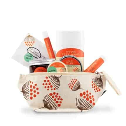 A cotton bag with an orange and brown flower pattern filled with orange-labeled beauty products.