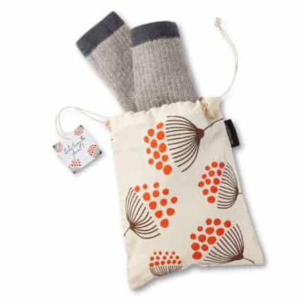 A cotton bag with an orange and brown flower pattern and gray socks peaking out.