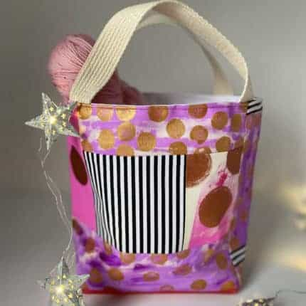A pink bag with gold dots and a black and white striped pocket.