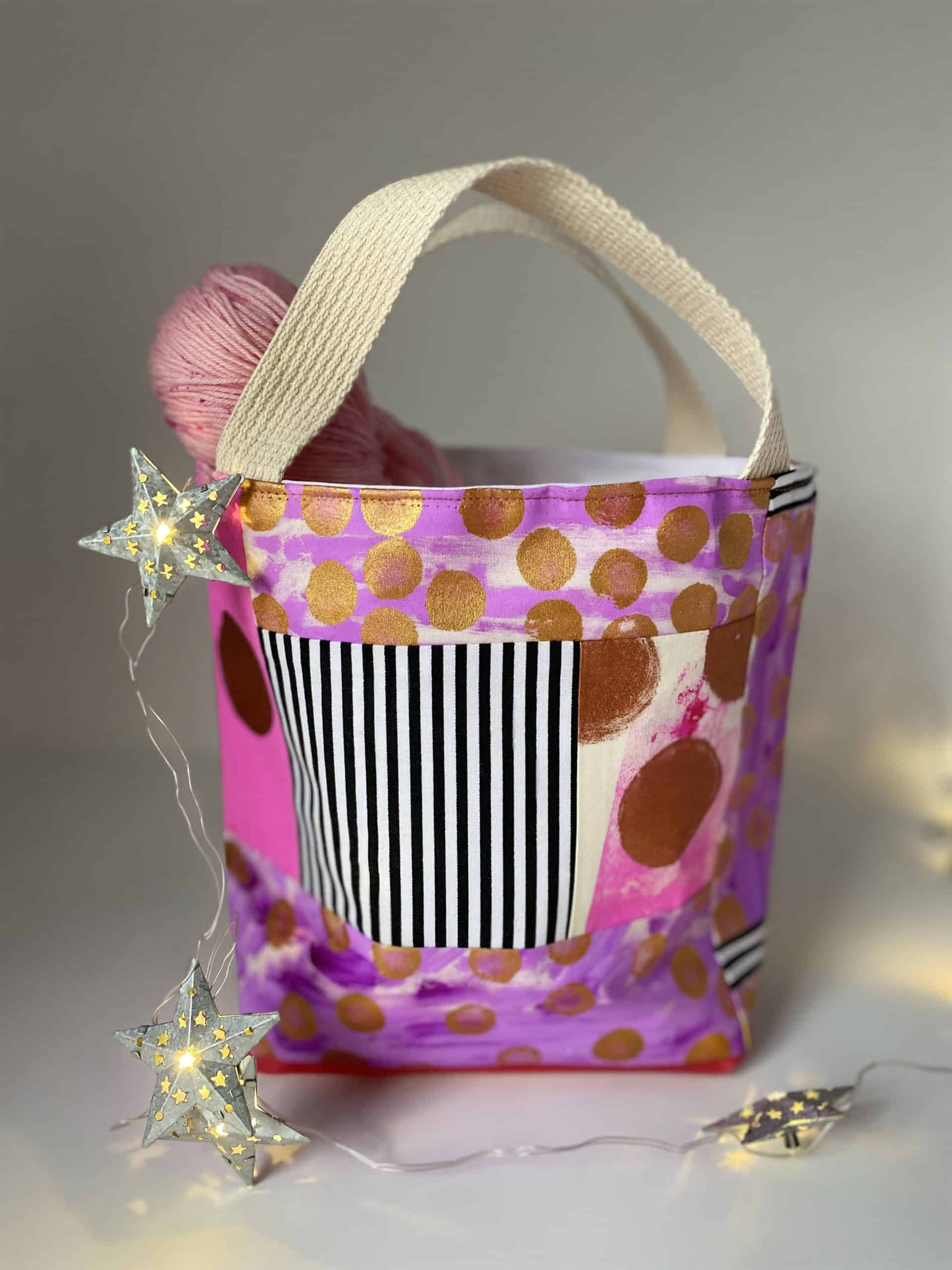 A pink bag with gold dots and a black and white striped p<a href=