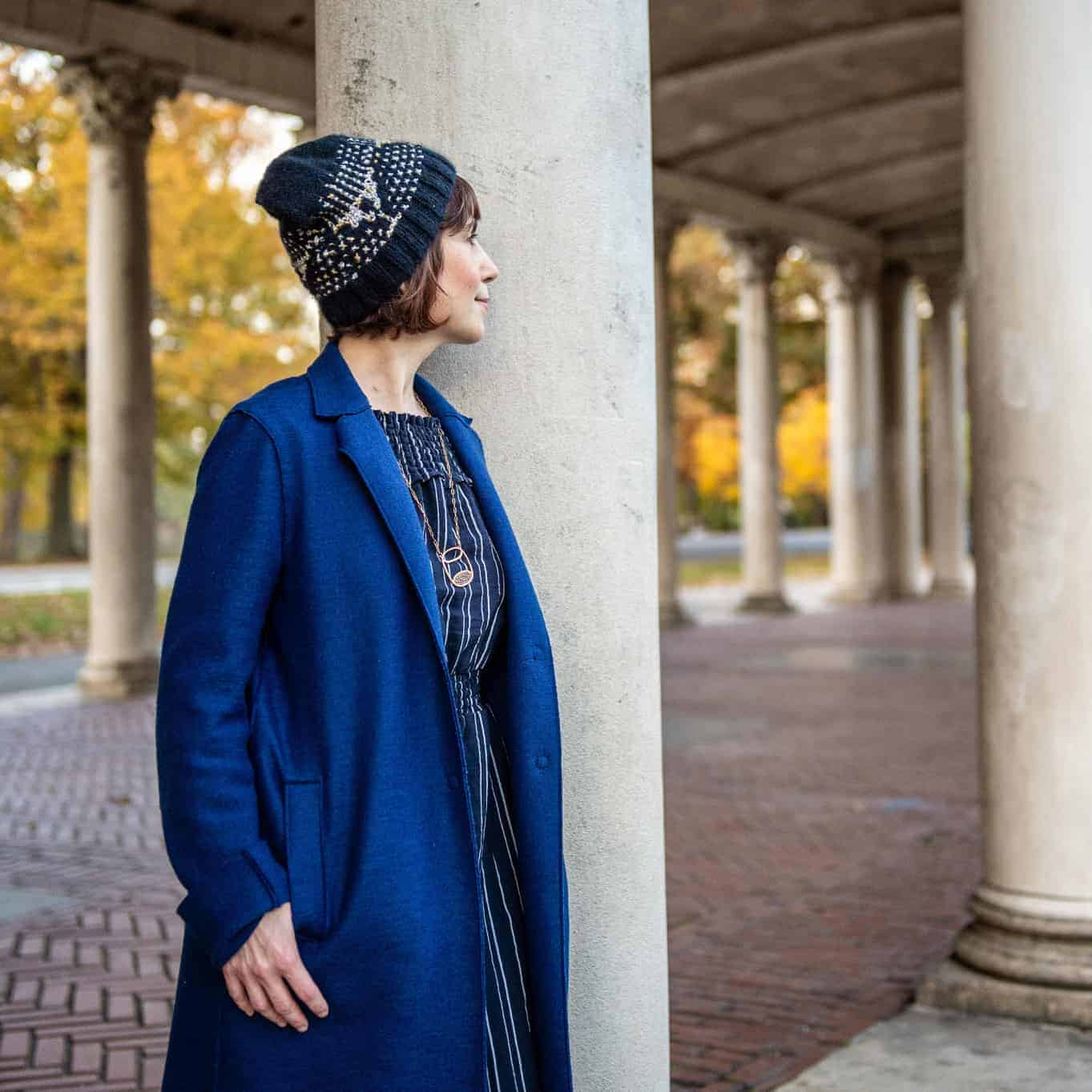 A woman models a blue and gray beanie next to columns.