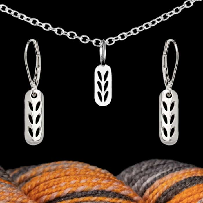 Silver jewelry above orange and gray yarn.