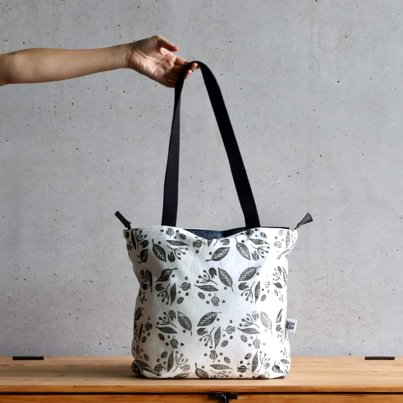 A white tote with a black floral print.