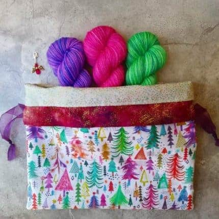 Purple, pink and green yarn peeking out of a bag with a print of colorful trees.