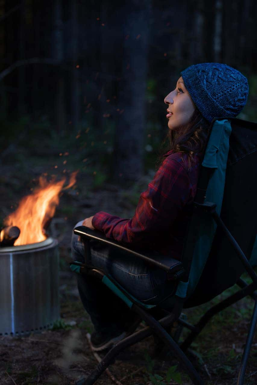A blue hat worn by a campfire.