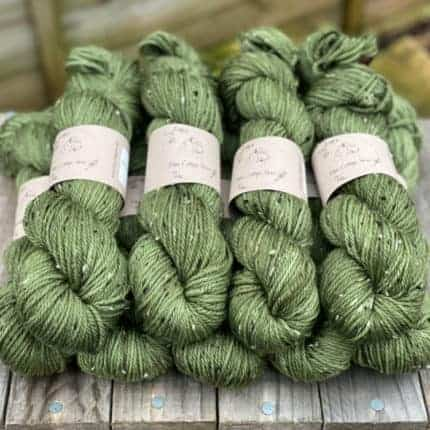 Green yarn with tweed neps.