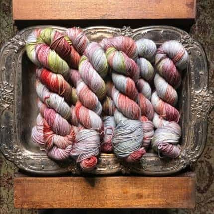 Yarn speckled with red, pink and green on a silver tray.
