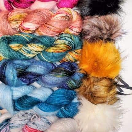 Multicolored skeins of yarn and faux fur pom-poms.