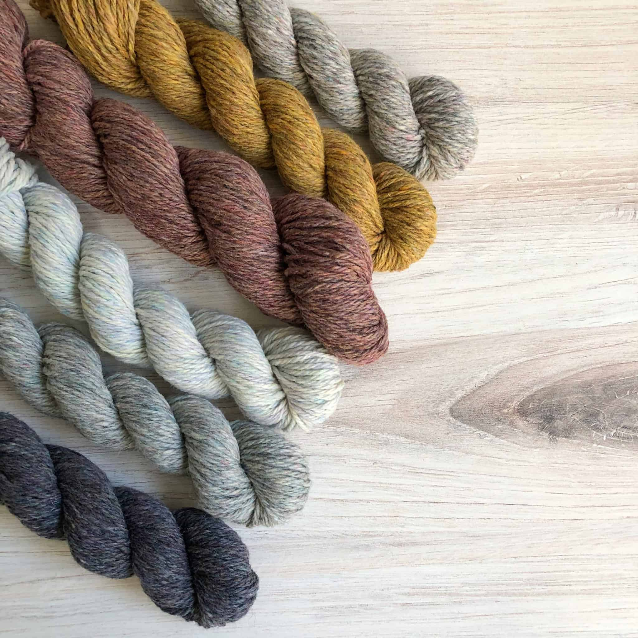 Skeins of gray, white, pink and gold yarn.