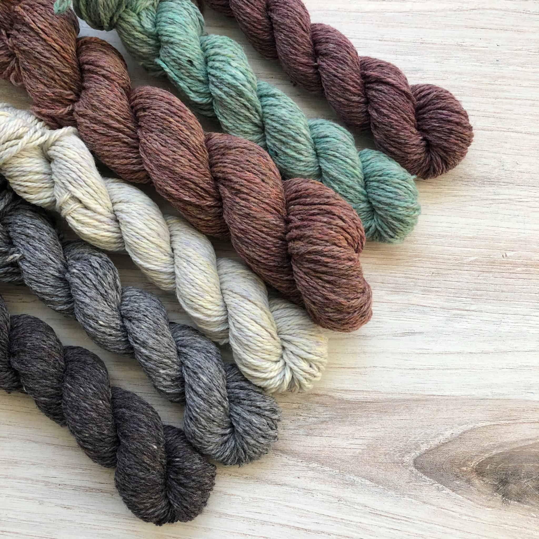 Six mini skeins of gray, white, purple and aqua yarn.