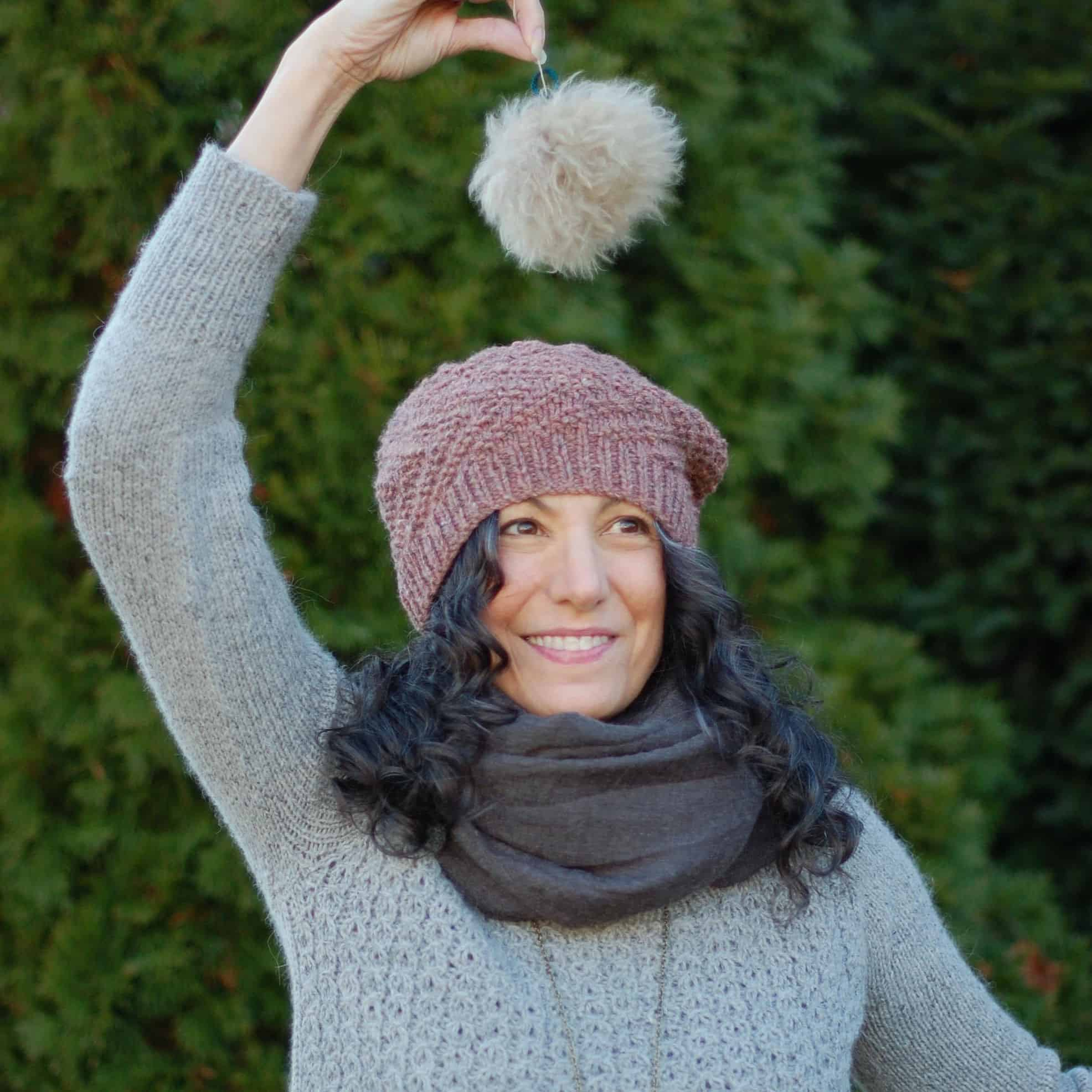 A woman holds a white fur pom-pom over a purple knit hat.