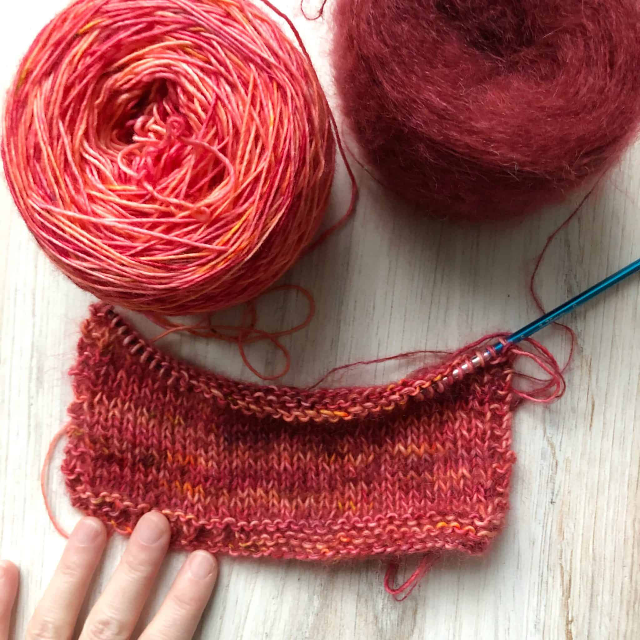 Cakes of red and purple wool and mohair yarn knit together in a swatch.
