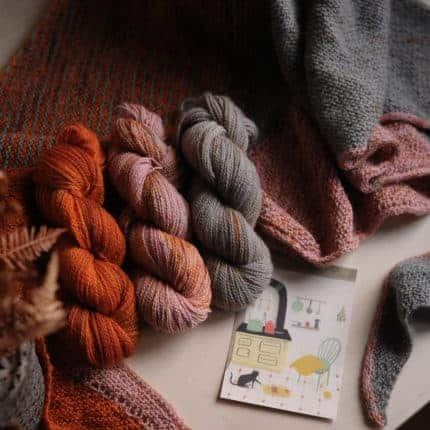 Skeins of orange, pink and gray yarn.