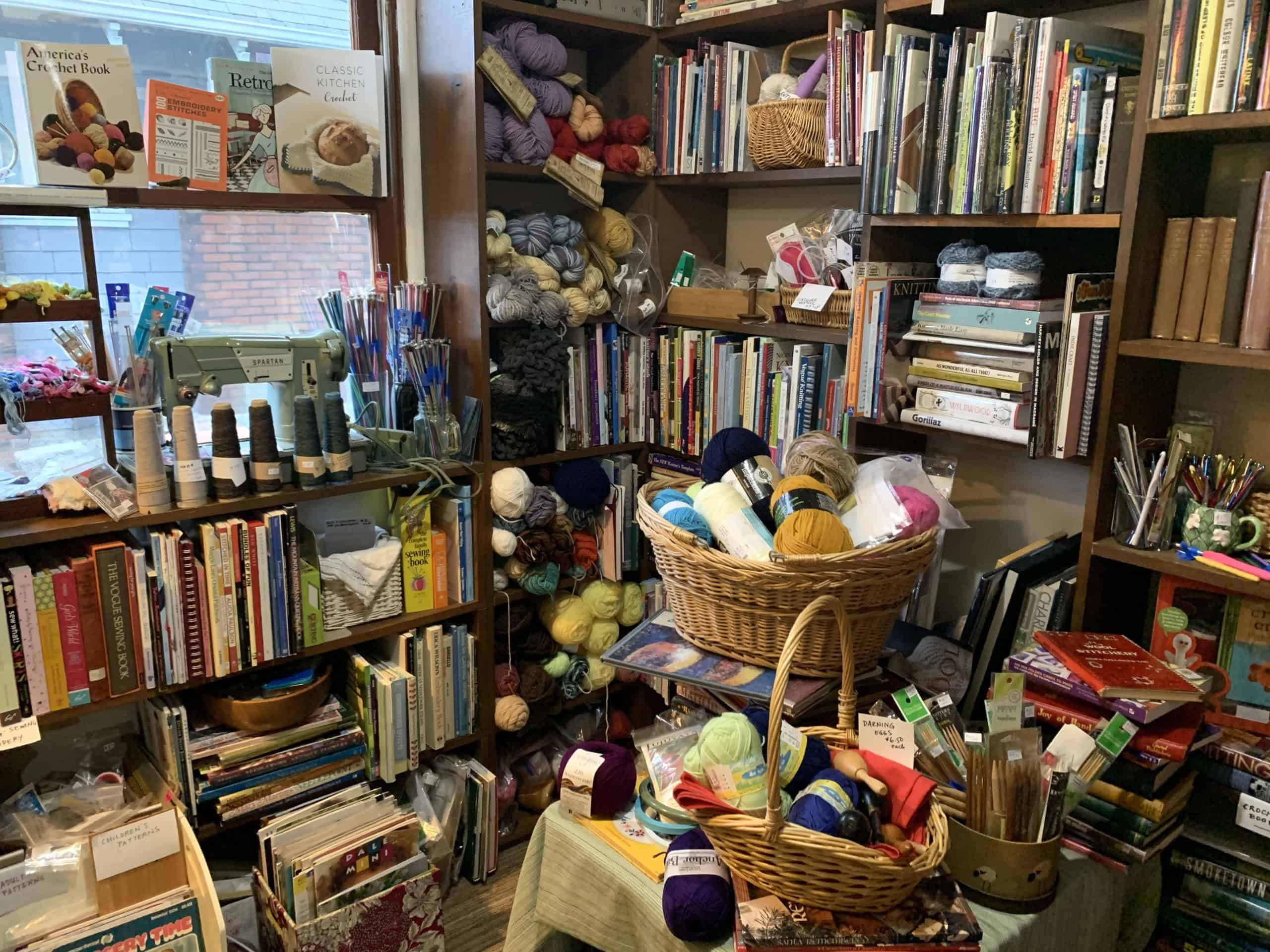 Shelves filled with books and yarn.