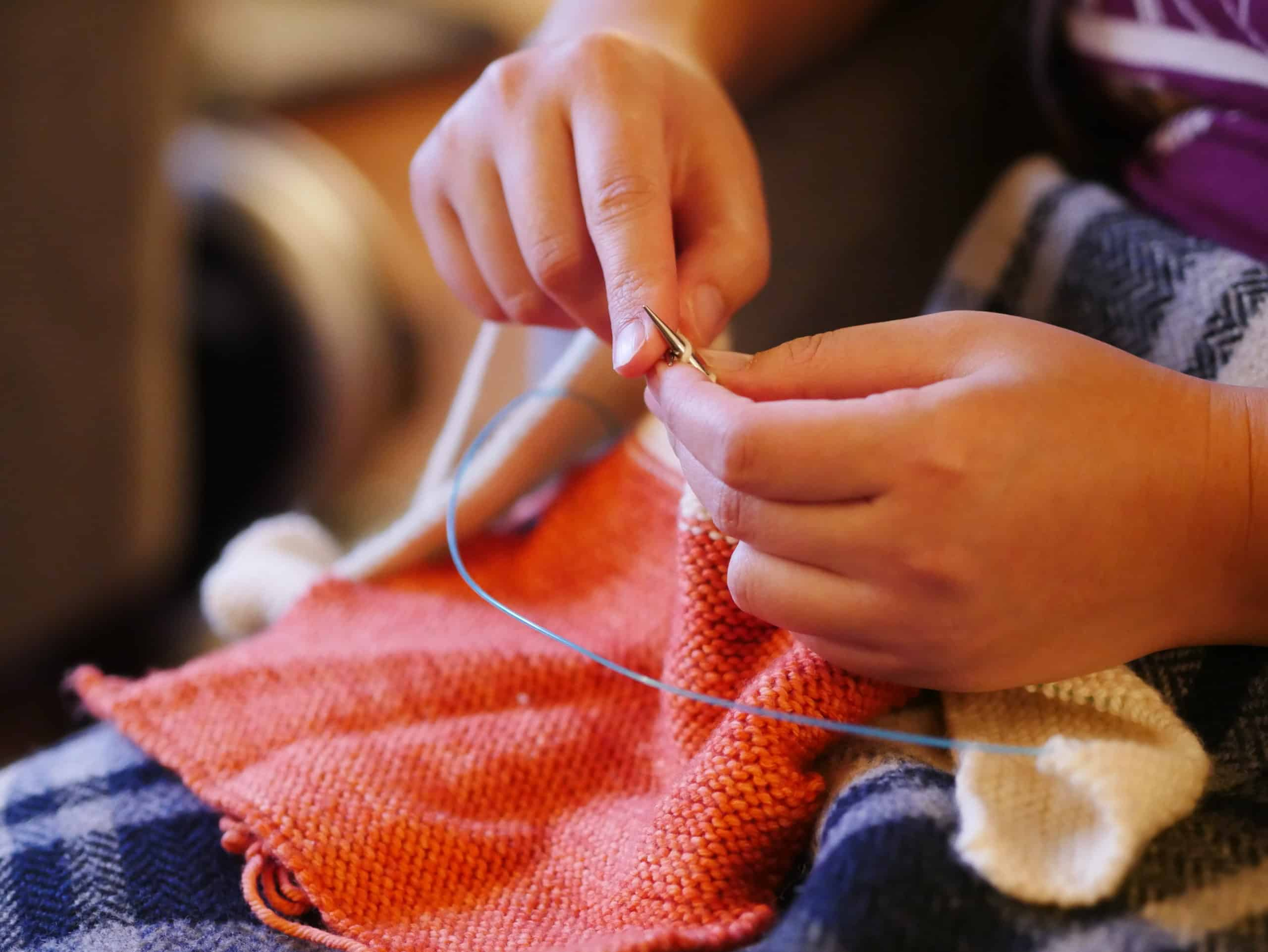 Hands knitting a coral sweater.