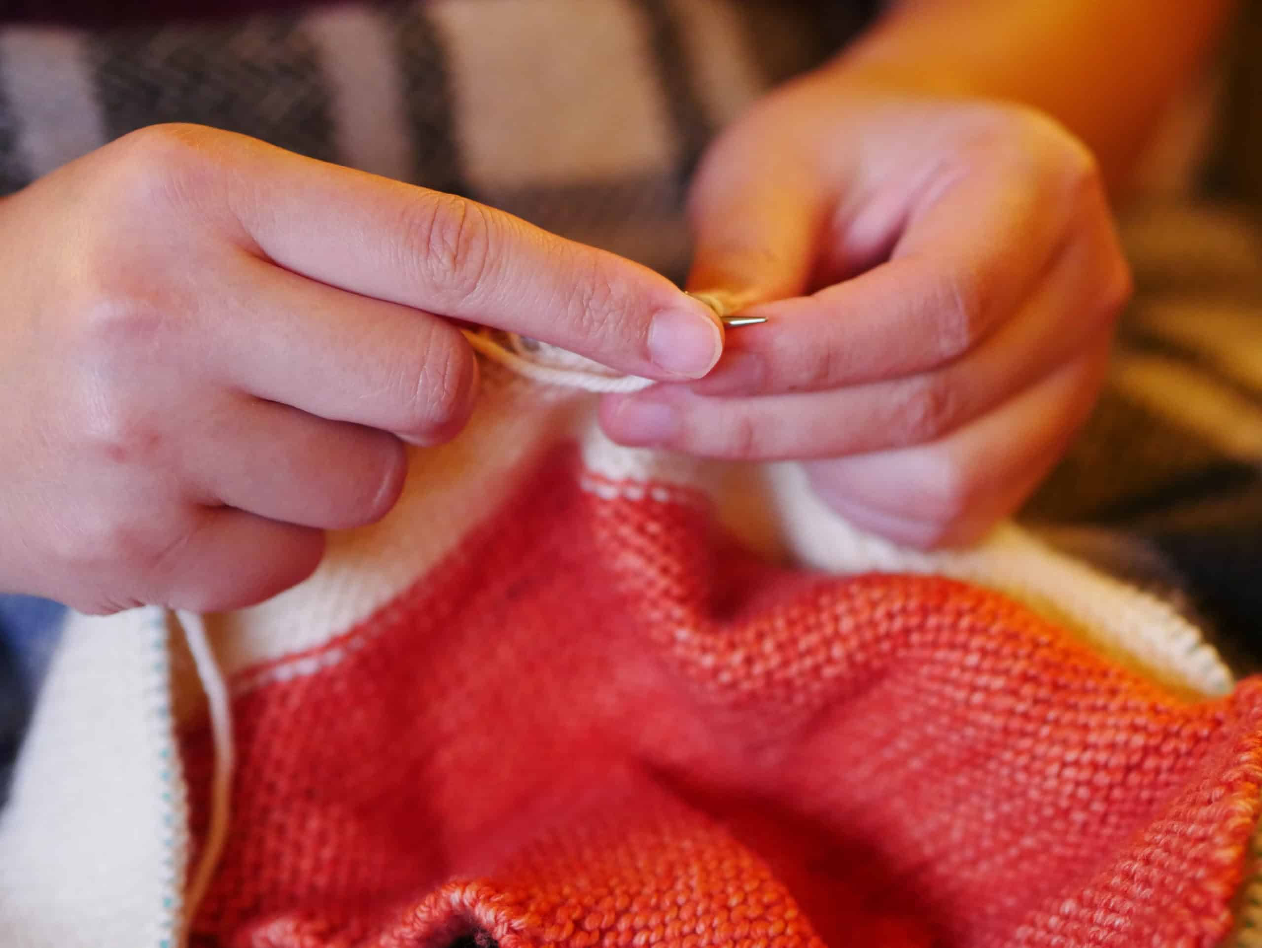 Hands knit a coral sweater.