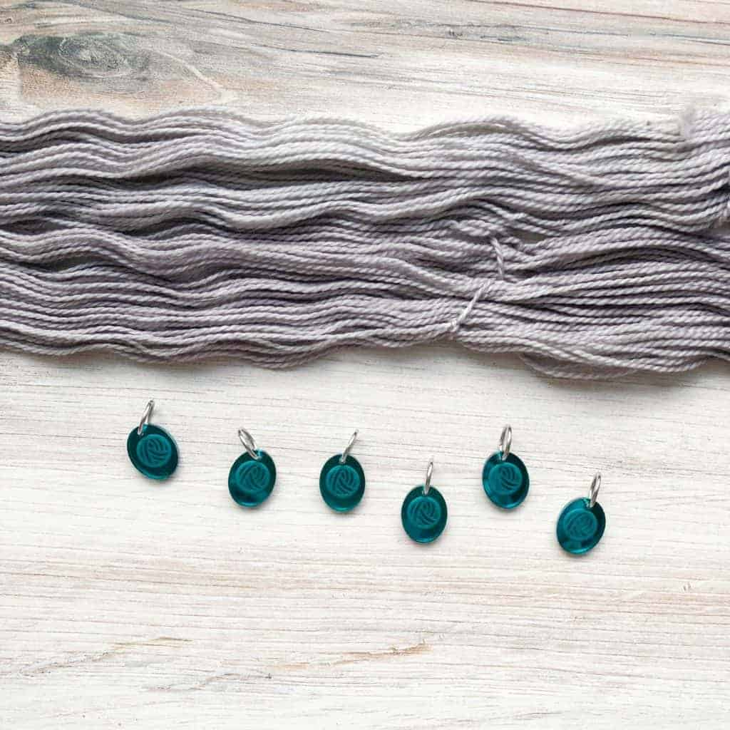 Oval teal mirror charms with a yarn ball.