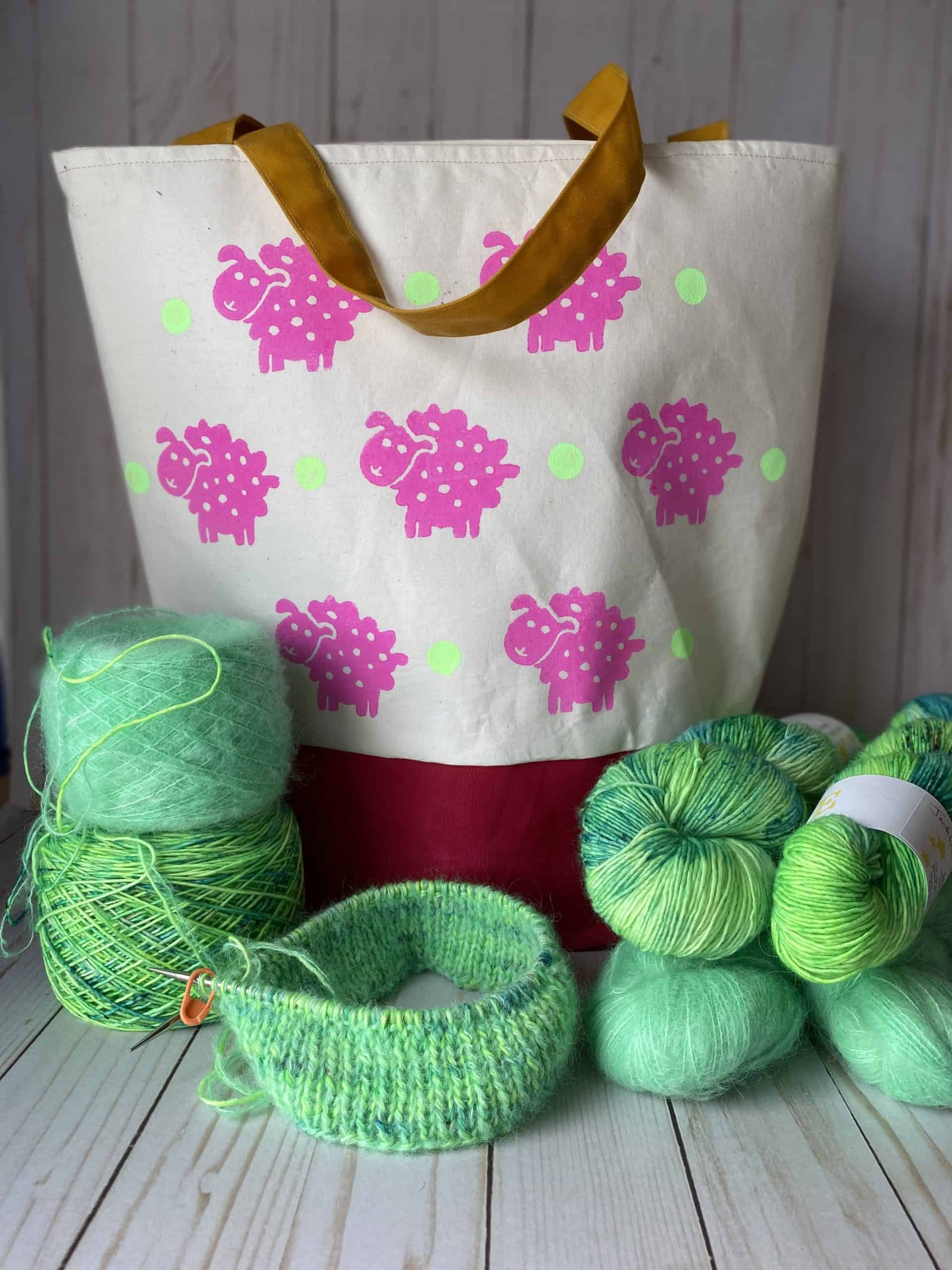 A white bag with magenta sheep surrounded by bright green yarn.