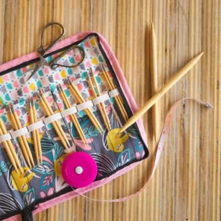A knitting needle case filled with wooden needles.
