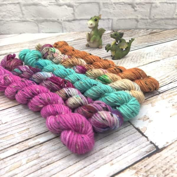 Skins of pink, purple speckled, green, beige and amber yarn.