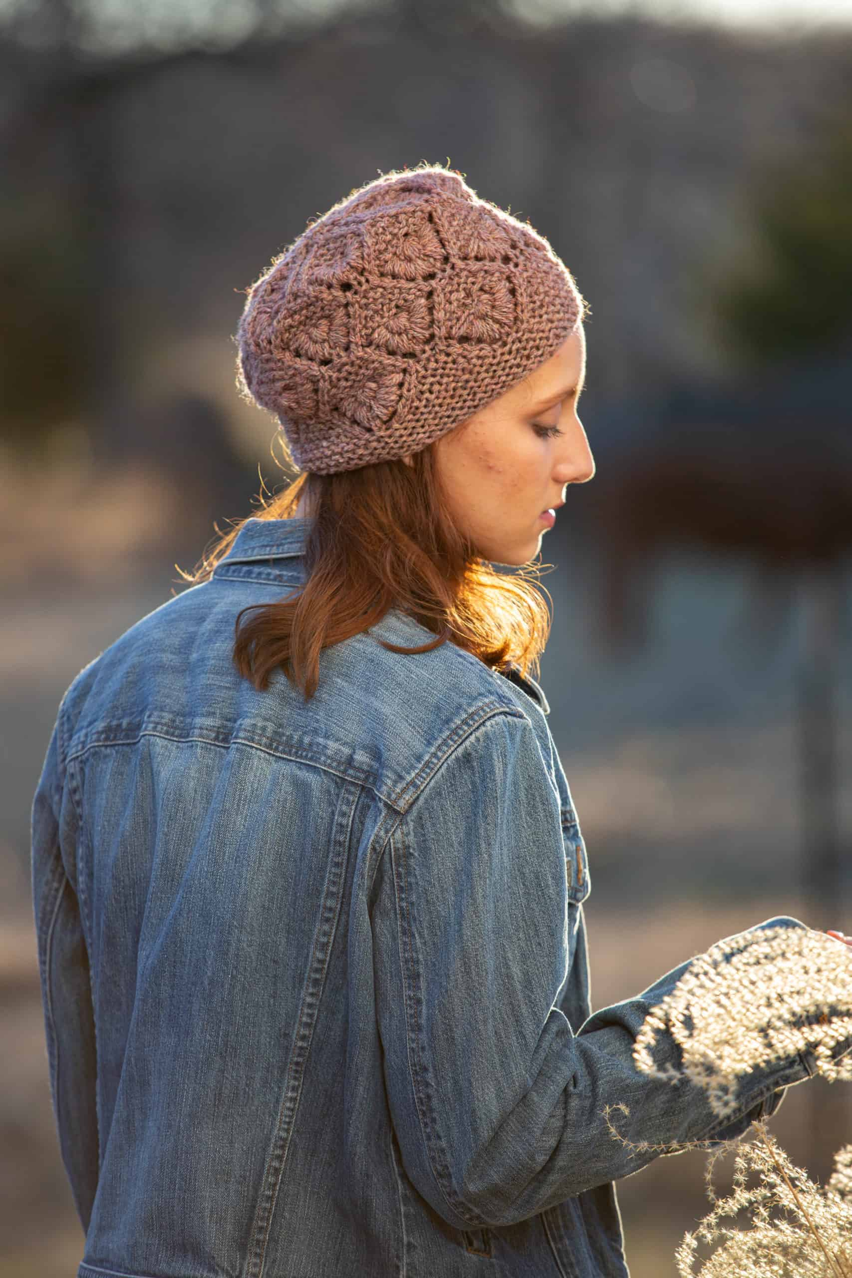 A dusky pink knit hat with a floral pattern.