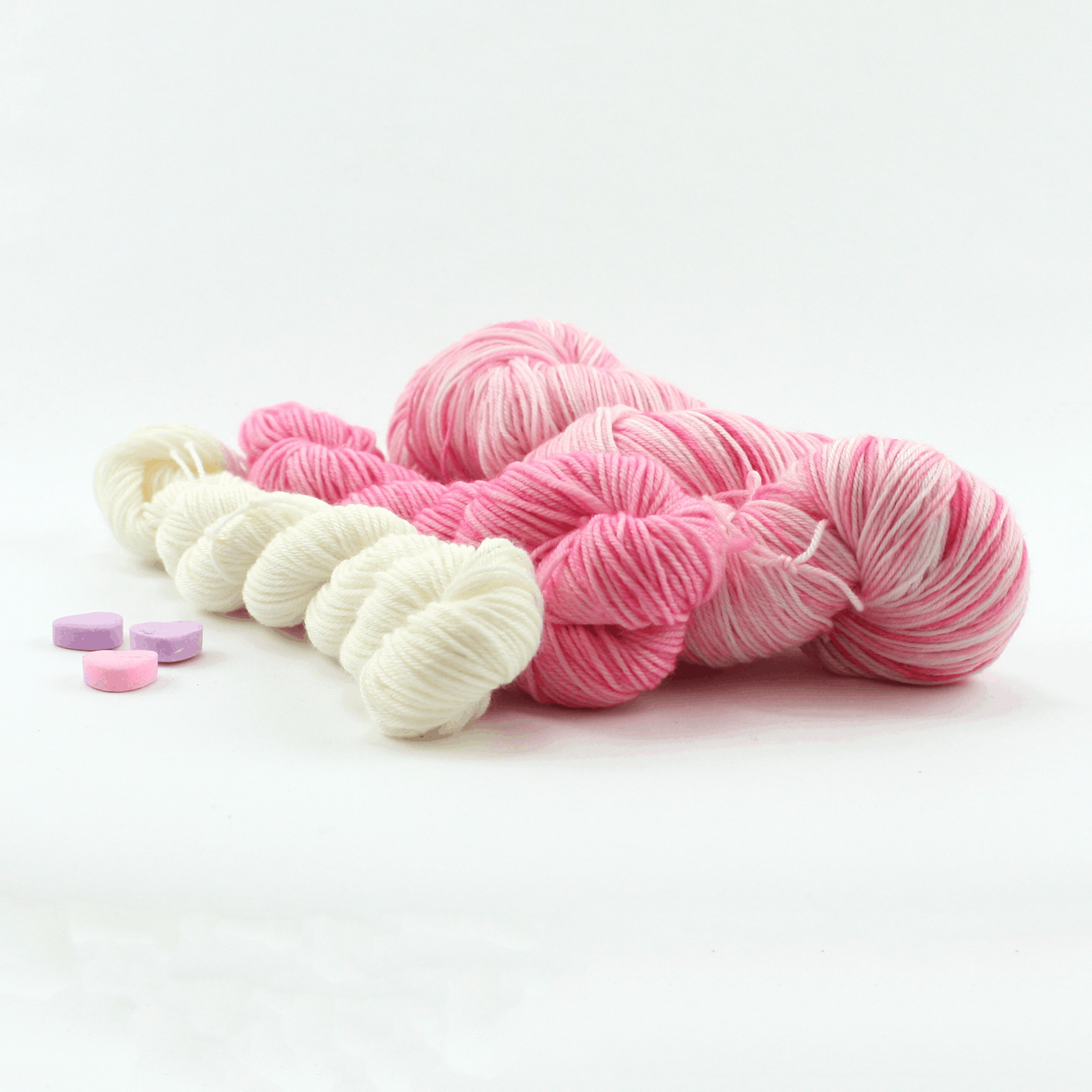 White and pink yarn with pink candy hearts.