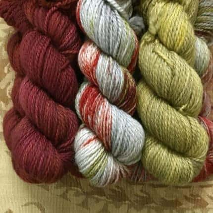 Skeins of red, gray speckled and green yarn.