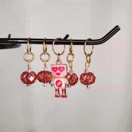 A pink robot stitch marker.