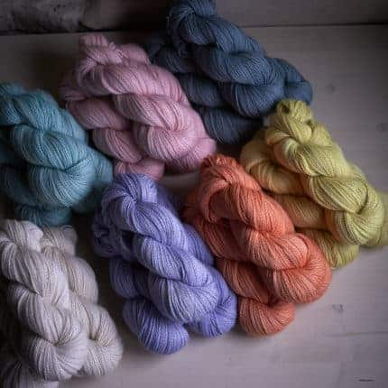 Skeins of white, blue, purple, pink, orange, yellow and navy yarn.