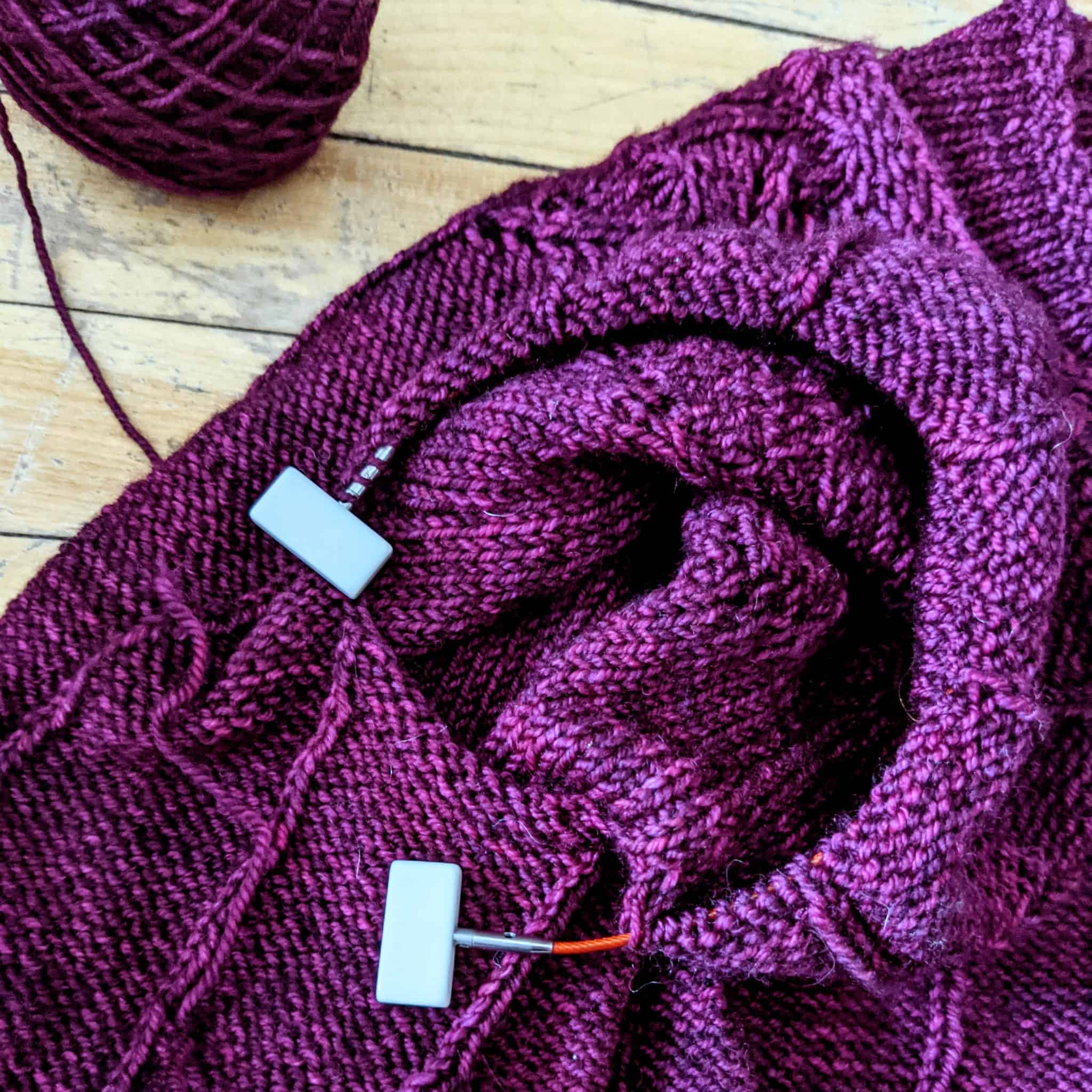 A purple knitting project on a red cord with white stoppers at the ends.